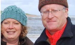 Woman and man in woolly hats, with Scottish loch in background