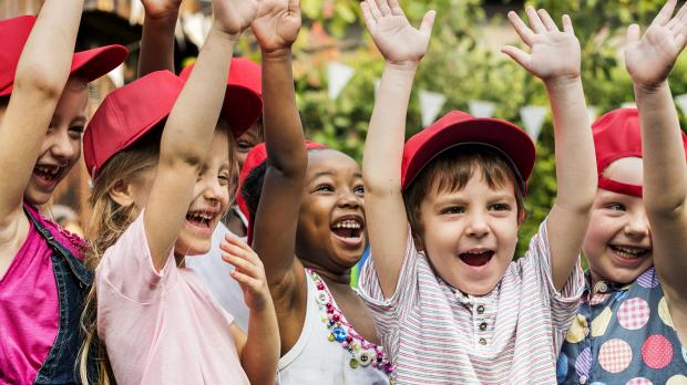 A group of young children in red caps laughing with their hands in the air