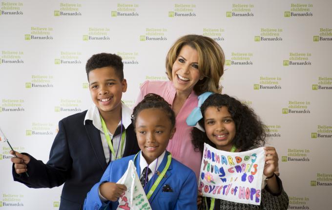 Natasha Kaplinsky and three children in school uniforms smiling