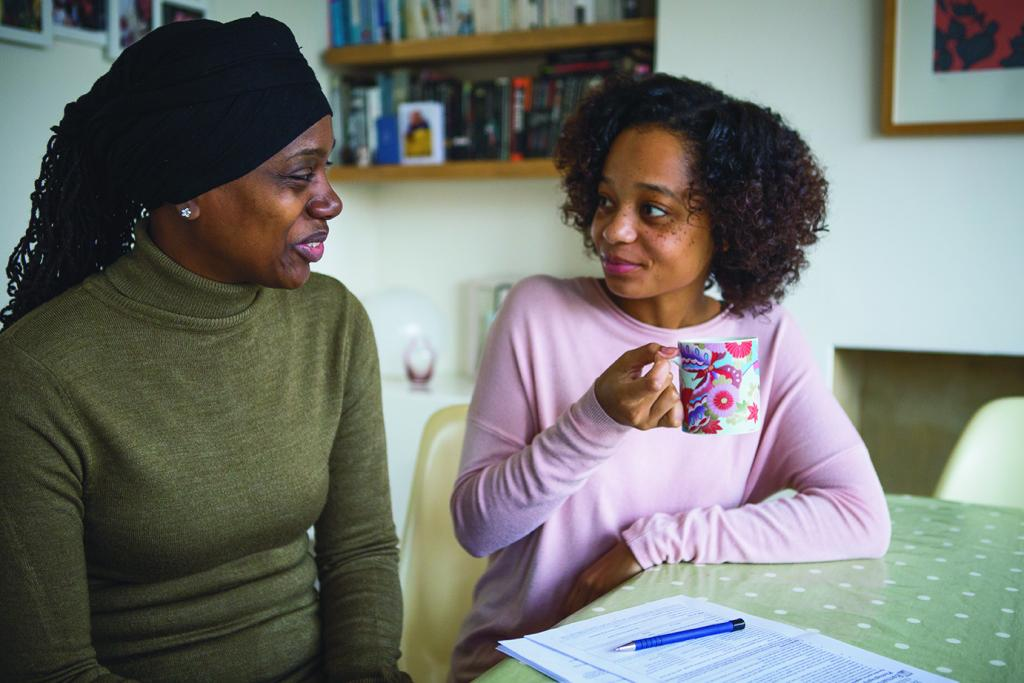 Young woman and care worker drinking tea and talking