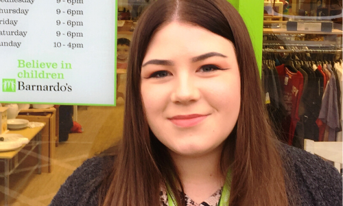 Apprentice Sophie standing in front of a Barnardo's store