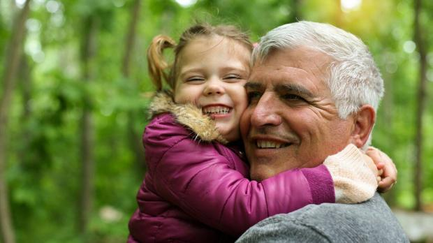 girl hugging grandfather and smiling