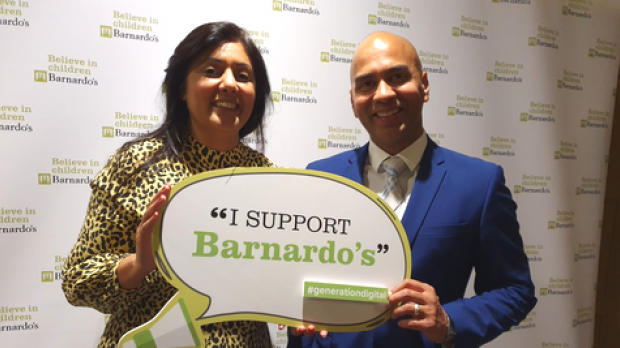 Nusrat Ghani MP and Sagar Sharma, Barnardo's Director of Communications, holding sign together at Conservative Party Conference