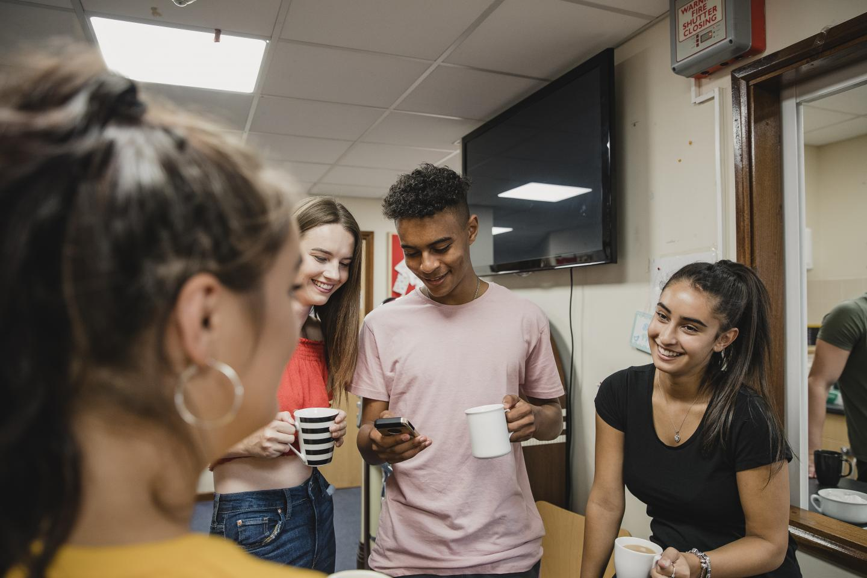 Teenagers in a room drinking tea