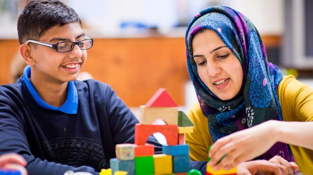 Woman in a hijab healping a young boy with glasses with playing blocks
