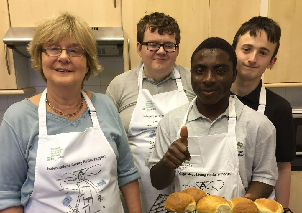 Barnardo's worker with young people baking bread