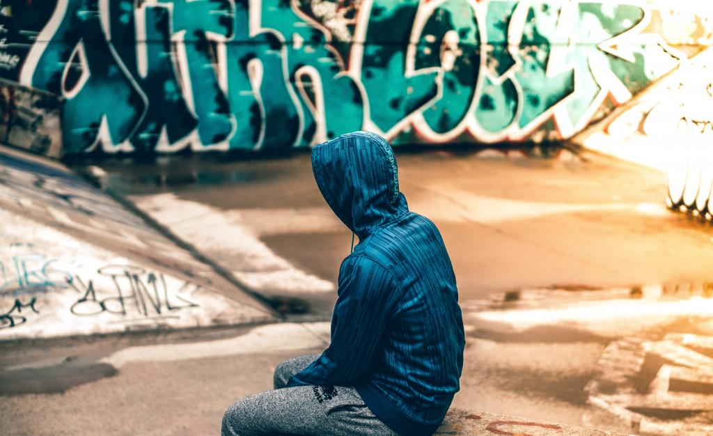Young person in hoodie sitting in skate park