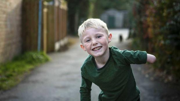 Young boy laughing in an alley