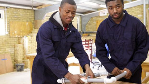 Two young men in coveralls working in a workshop
