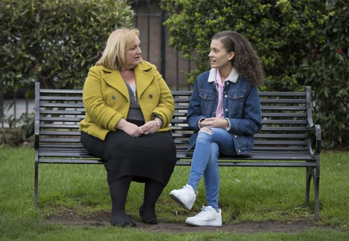 A young girl and a woman sit talking on a bench in a park