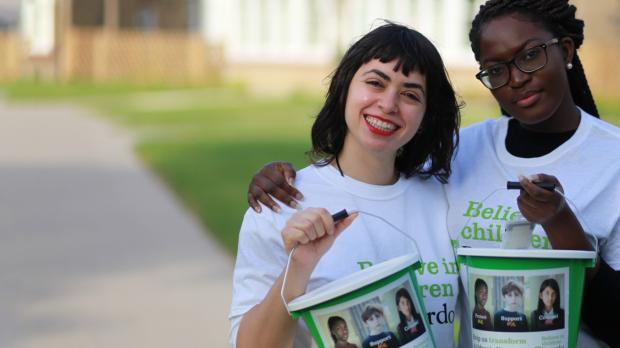 2 young people in Barnardo's t-shirts with fundraising buckets