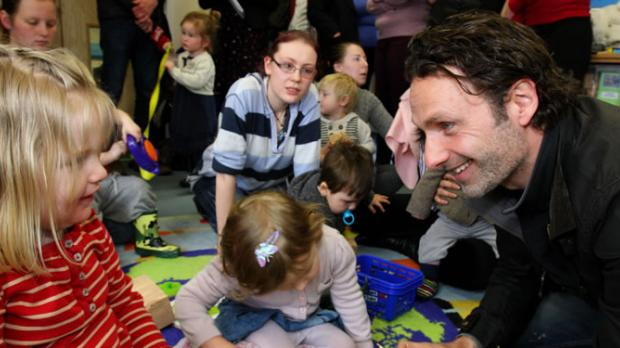 A group of adults and children playing and smiling on the floor of a nursery