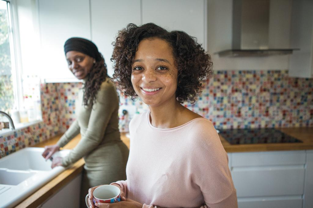 Young person smiling at camera with adult at sink in background