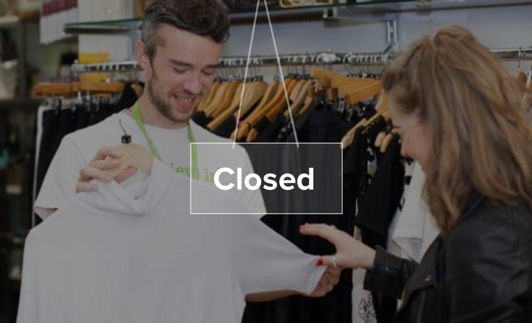 Barnardo's volunteer with customer in charity store with closed sign overlaid