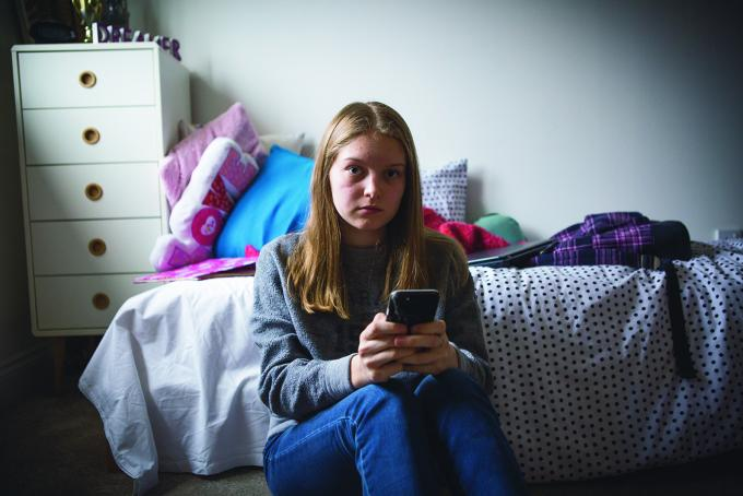 Girl sitting in front of bed holding a mobile phone