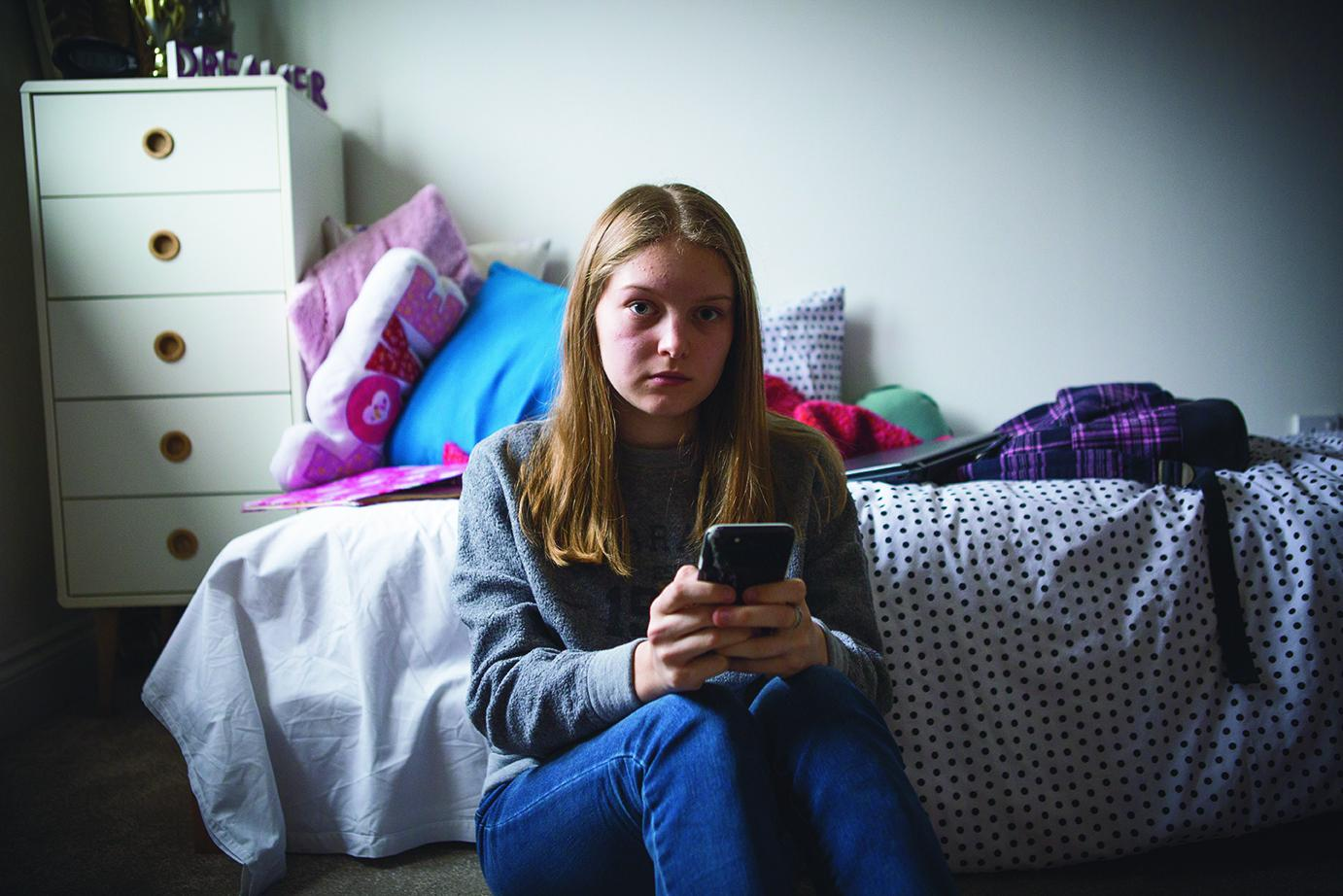 A young girl sitting on the floor of her bedroom holding a mobile phone