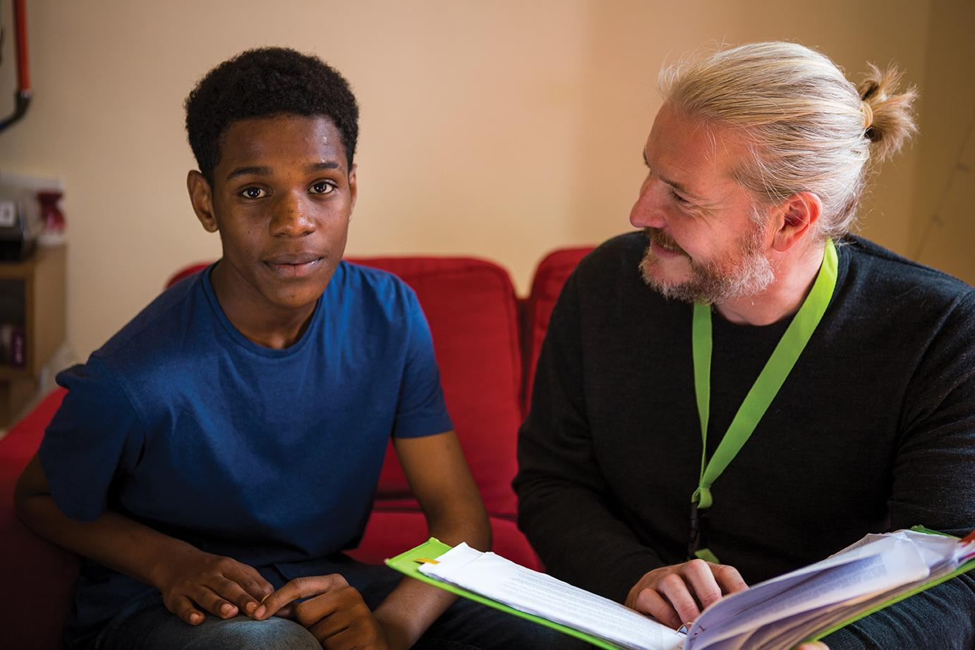 Barnardo's project worker sitting with young person on a sofa