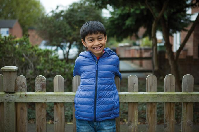 Young boy smiling in front of fence