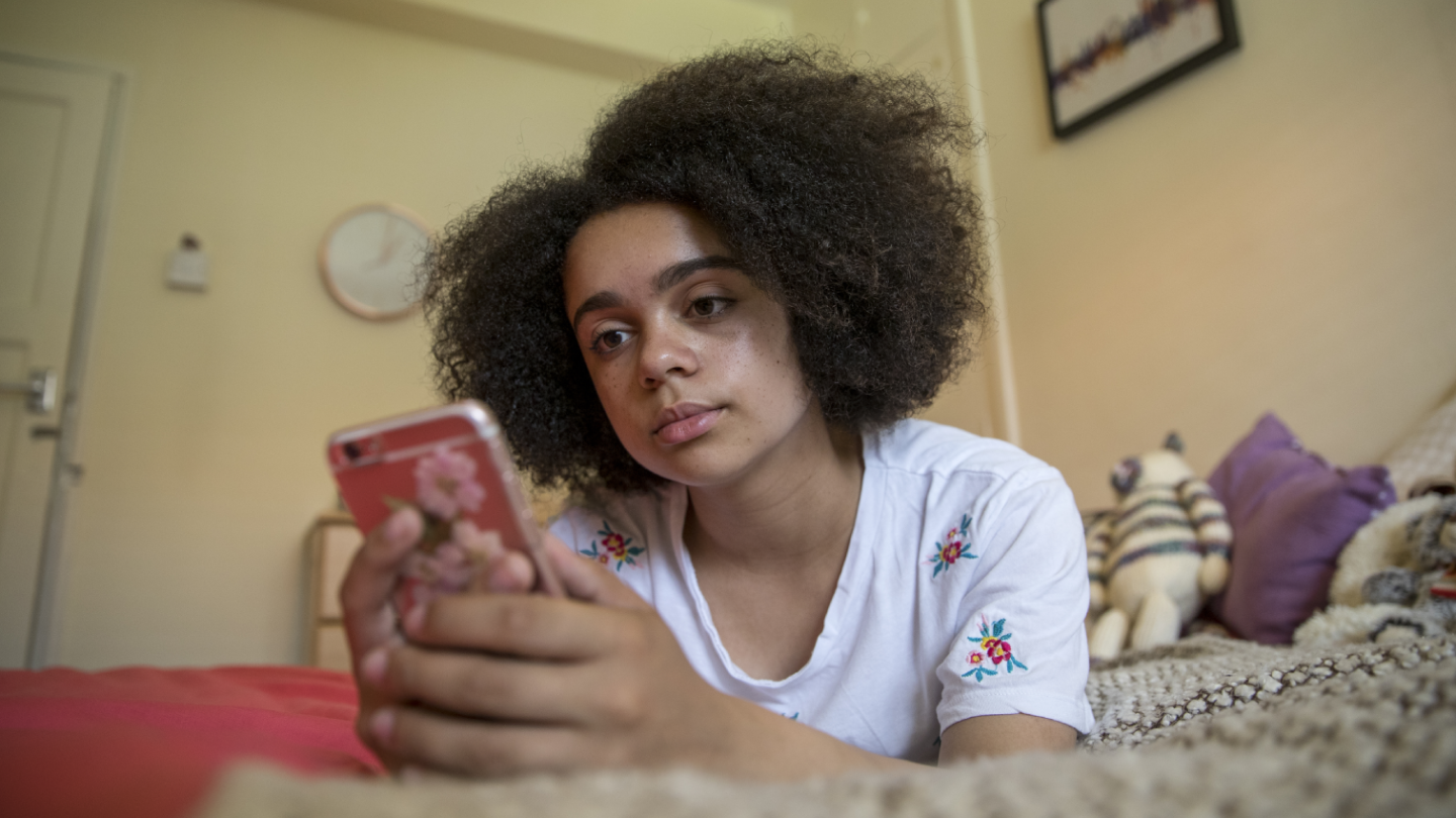 Young girl laying on bed and looking at a phone