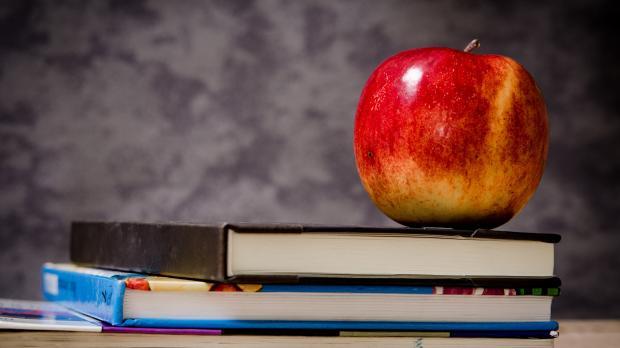 Apple sitting on books on a teachers desk