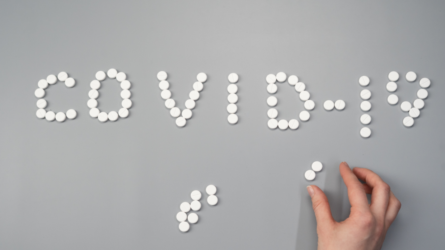 Pills spelling out the word COVID-19