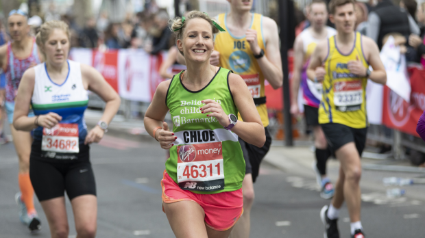 Woman smiling and running in a marathon wearing a Barnardo's jersey