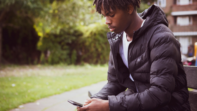 Young man texting sitting on a bench in a park