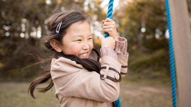 Smiling girl playing on a swing