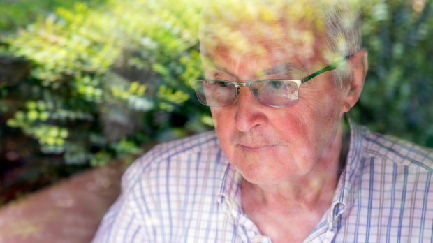 Older man looking out of window