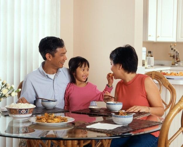Parents and young child sitting at dining table
