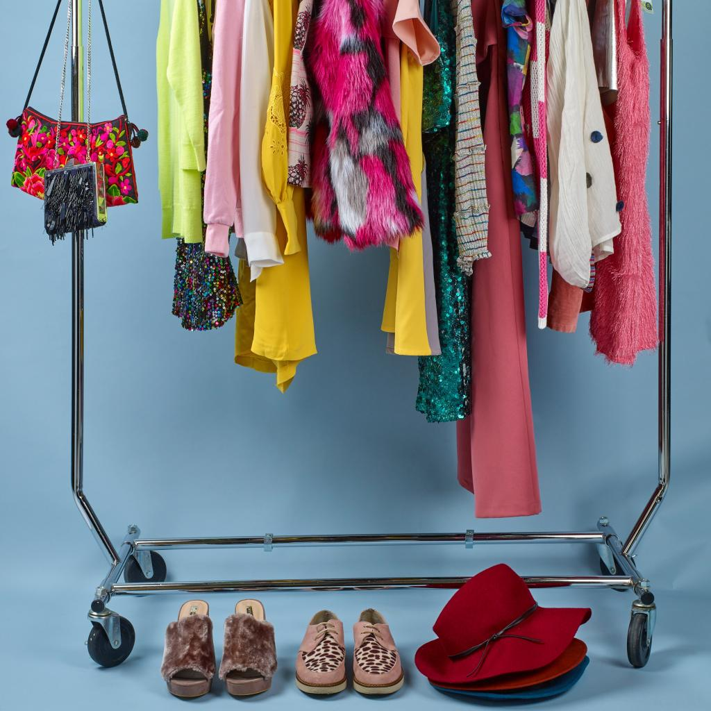 Clothes on rack with shoes and hats