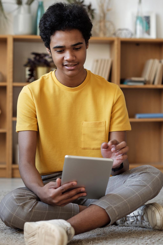 Teenage boy sitting and playing with an ipad