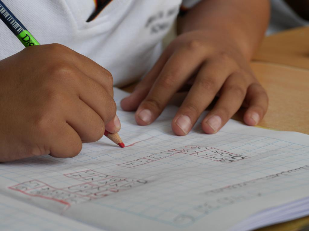 Close up of young person's hands writing in a school book