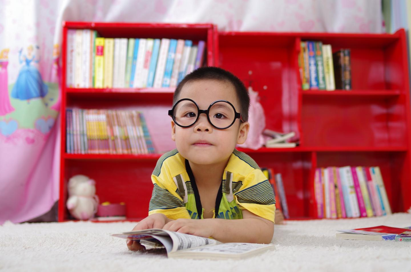 Young boy wearing glasses reading at school