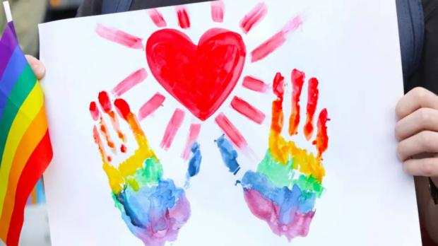 Painted rainbow handprints underneath a painted red heart