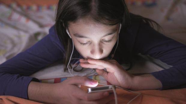 Young person laying down looking at screen