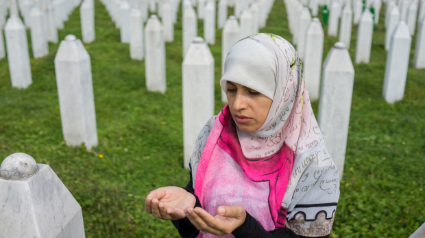 Srebrenica Memoral Week - woman praying at a grave