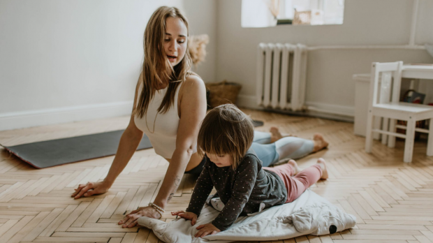 Mother and young daughter practising yoga together