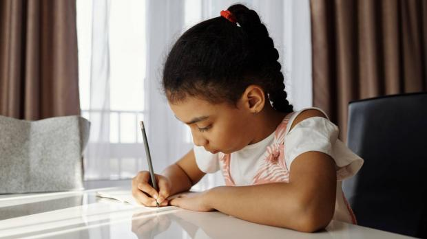 Young girl writing in book