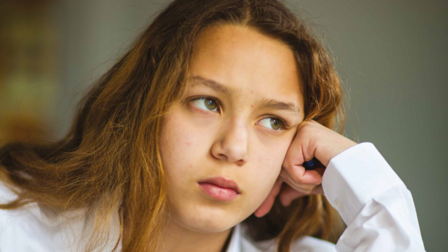 Girl in school uniform resting head on her hand while looking into the distance