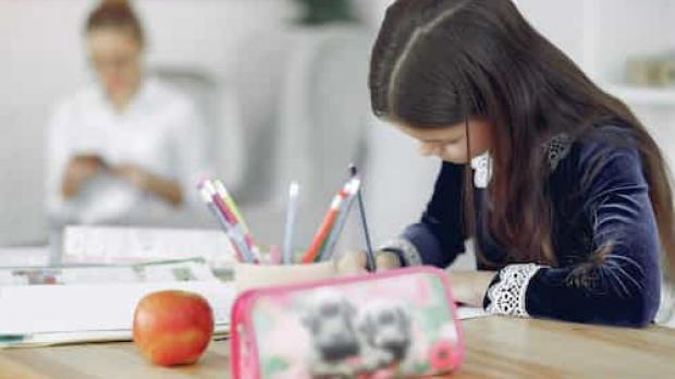 A young girl writing at a desk with an apple, pencil case and pencil pot.