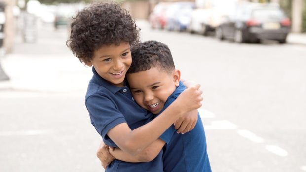Two young brothers hugging and smiling
