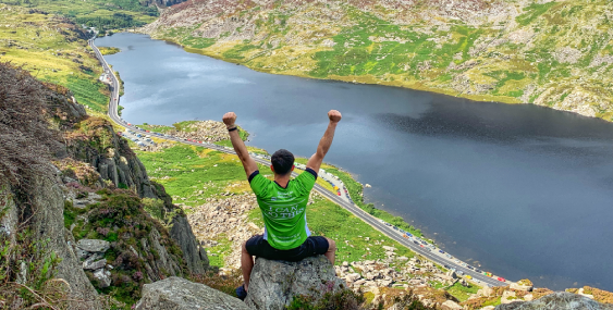 Man in Barnardo's jersey raising arms in victory on top of a mountain