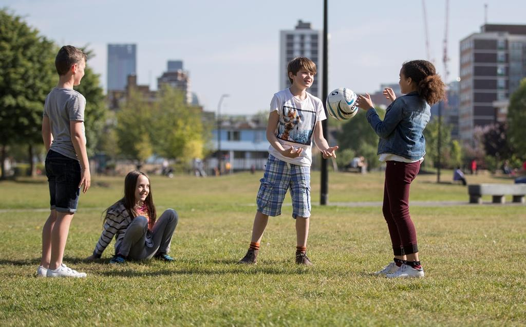 Four children playing with a pall in a city park