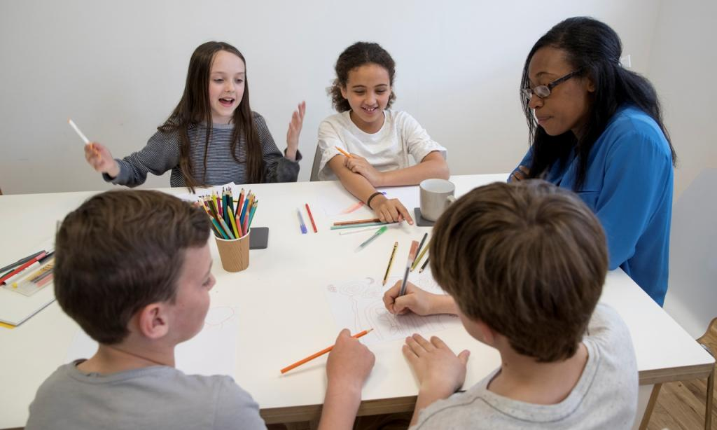 Group of children colouring at table with support worker