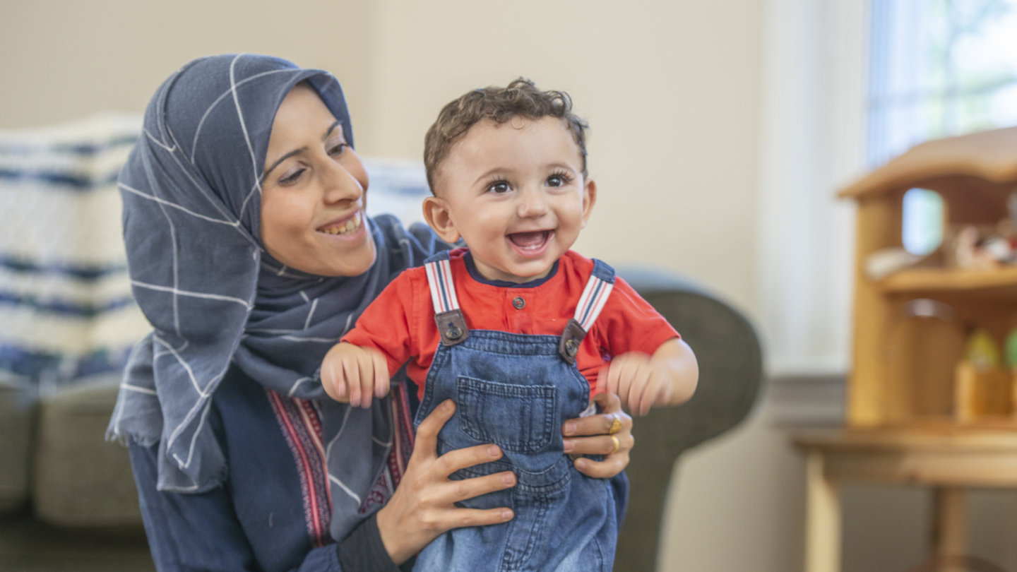 Muslim mother laughing with her baby son